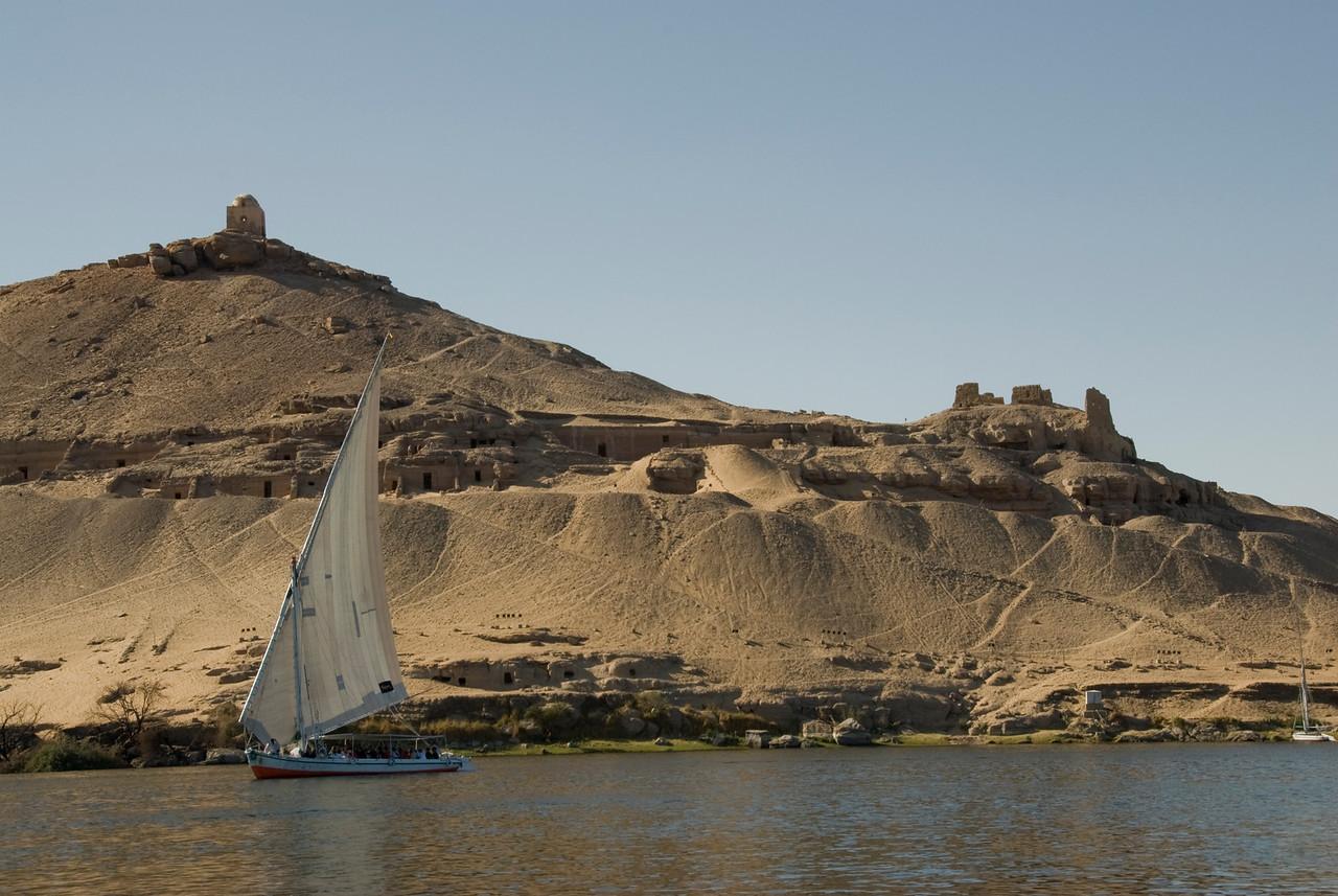 Felucca against sand cliff along Nile River- Aswan, Egypt