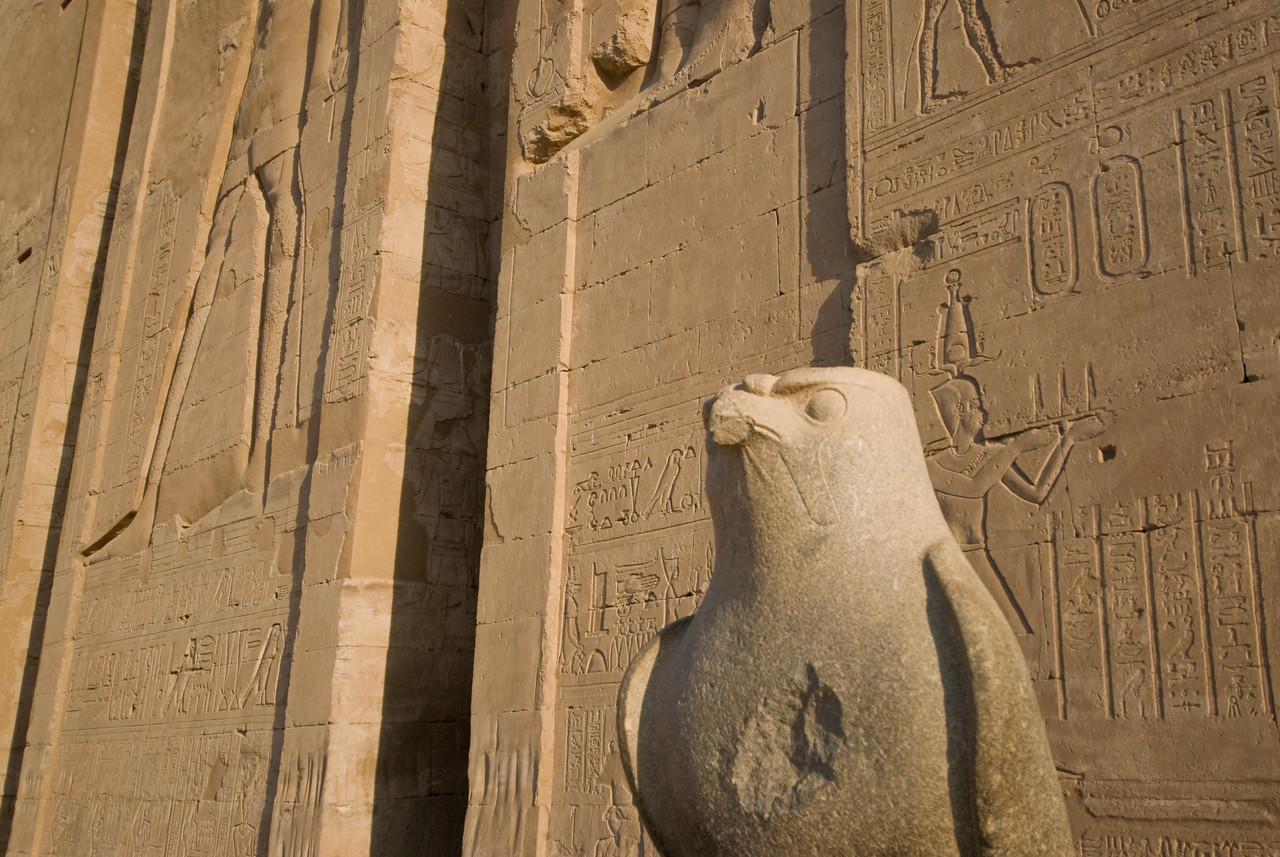 Falcon Statue against heiroglyphic wall at Edfu Temple - Edfu, Egypt