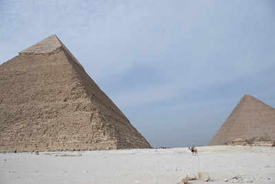 Camel-riding man in the middle of two pyramids - Giza, Egypt