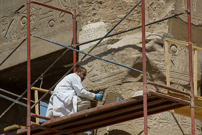 Closer shot of a restoration worker at the Luxor Temple - Luxor, Egypt