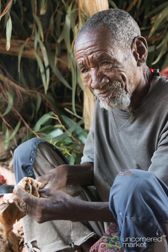 Elder Ethiopian Man Cutting Meat - Lalibela, Ethiopia