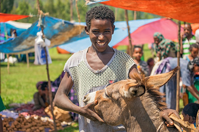 Ethiopian boy with his donkey at a market  in Ethiopia