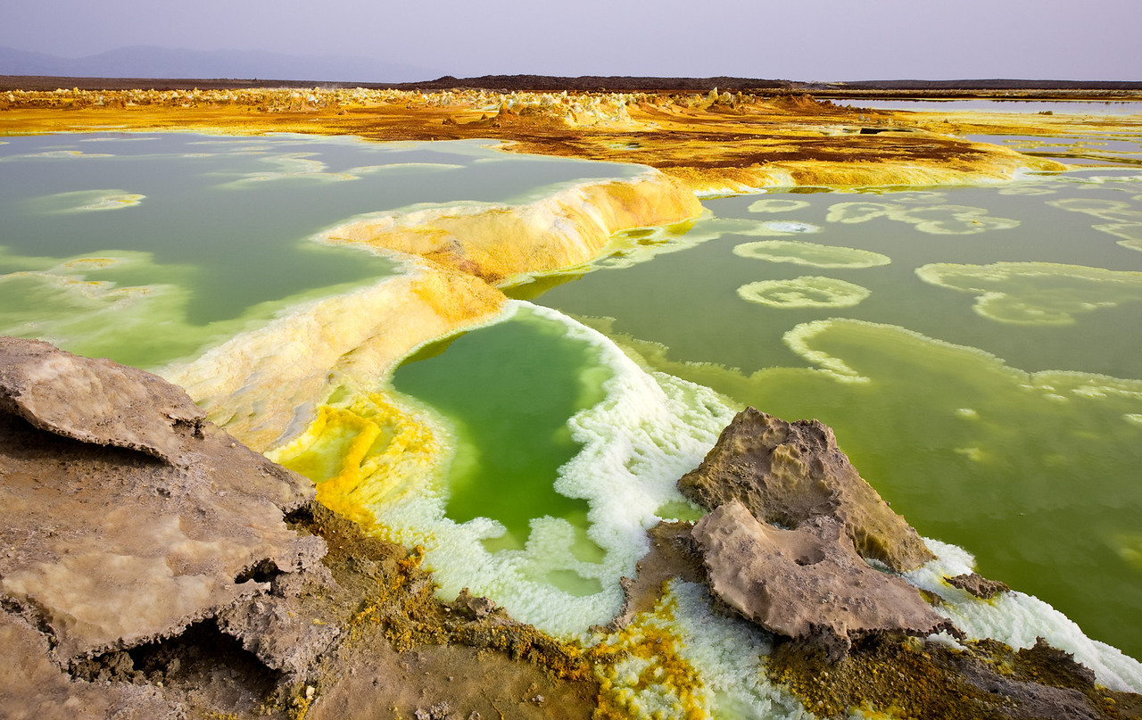 Lurid technicolor-green corrosive acid ponds and bubbling orange sulfur vents, not to mention the extreme heat give this area a decidedly sinister otherworldly aspect.<br /> <br /> Location: Dallol, Denakil Depression, Ethiopia<br /> <br /> Lens used: 10-22mm f3.5-4.5