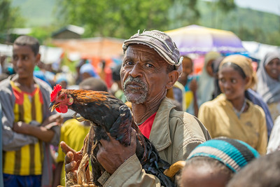Old ethiopian man selling a rooster in a market