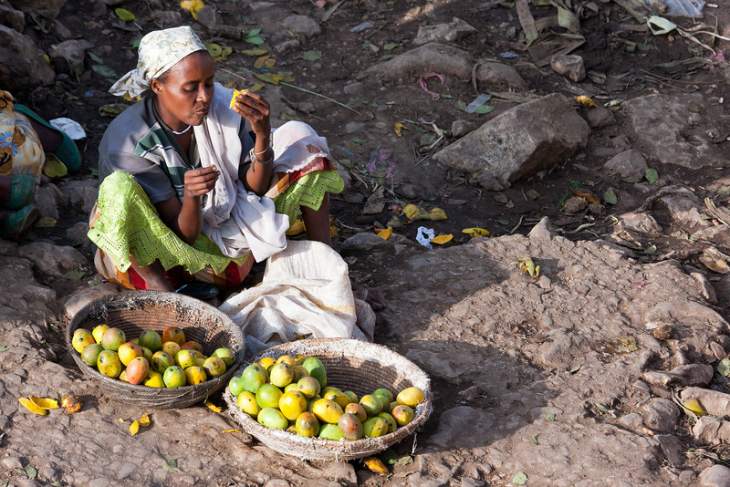 A mango vendor dippin' into her own supply.<br /> <br /> Location: Harar, Ethiopia<br /> <br /> Lens used: 100-400mm f4.5-5.6 IS