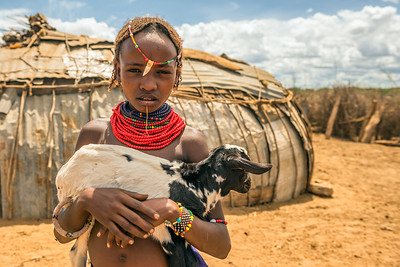 Girl from the African tribe Dasanesh holding a goat