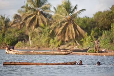 BRENU AKYINIM, GHANA - OCTOBER, 2006: Young boys playing in the water around a canoe. The fishing village of Brenu-Akyinim is located 10 km west of Elmina and features a long palmfringed sandy beach often packed with fishermen and their boats.  ( Photo by: Christopher Herwig)