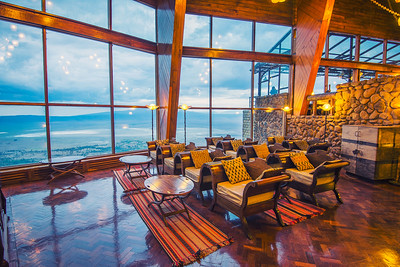 Interior of the Ngorongoro Wildlife Lodge with a glass wall overlooking the park