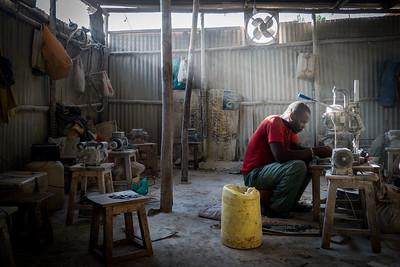Grinding bone into jewelry in Kibera