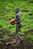 Young Suri herdsman with blood bowl, morning. South Omo, Ethiopia