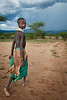 Young girl walking home, approaching storm. Omo Valley, Ethiopia