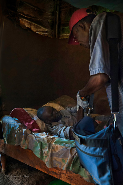 Sadimba, rural health caregiver attending HIV/AIDS patient at home. Ugenya, Kenya.