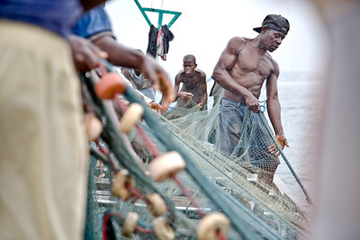 Kwame Atta and his fellow Liberian and Ghanain fishermen out fishing the waters around Monrovia, Liberia in the rainy season. The fishing industry is an important source of employment and food for Liberians and is increasingly under threat by better equipt and unregulated foreign vessels over fishing in its unprotected waters.