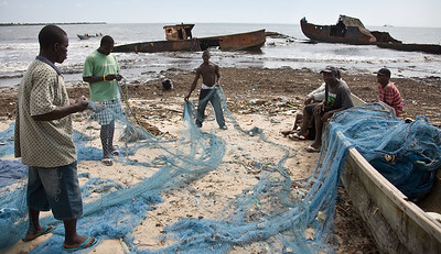 Young fixing fishing nets with  rusted fishing boats in the background at Point Four Beach near the Port of Monrovia.   Liberia has 570 kilometres of coastline, and there have always been plenty of fish to catch out at sea. But now foreign boats are fishing in the region, both legally and illegally, and the traditional fishing communities are noticing a marked decrease in the number of fish they are catching. The equipment they use simply can't compete with the large scale trawlers.