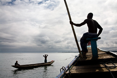 Liberian and Ghanain fishermen on a Fanti fishing boat searching the waters around Monrovia, Liberia for any sign of a school of fish. The fishing industry is an important source of employment and food for Liberians and is increasingly under threat by better equipt and unregulated foreign vessels over fishing in its unprotected waters.