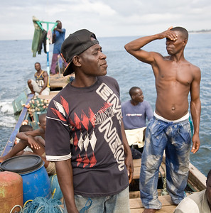 Kwame Atta in the black Eminem shirt with his fellow Liberian and Ghanain fishermen on a Fanti fishing boat searching the waters around Monrovia, Liberia for any sign of a school of fish. The fishing industry is an important source of employment and food for Liberians and is increasingly under threat by better equipt and unregulated foreign vessels over fishing in its unprotected waters.