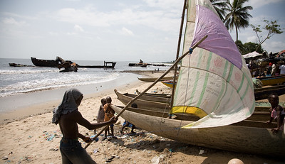Young boy tests his sail at Point Four Beach near the Port of Monrovia.   The Liberian Government is concerned about the big foreign boats affecting the livelihoods of fishing families. It has implemented an exclusion zone of three nautical miles for big boats, with plans to improve enforcement, monitoring and standards.