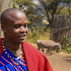 "Maasai warrior in his boma with a ""Maasai Jeep"" in the background.  Walking is the only mode of transportation for the Maasai.  Donkey is the beast of burden."