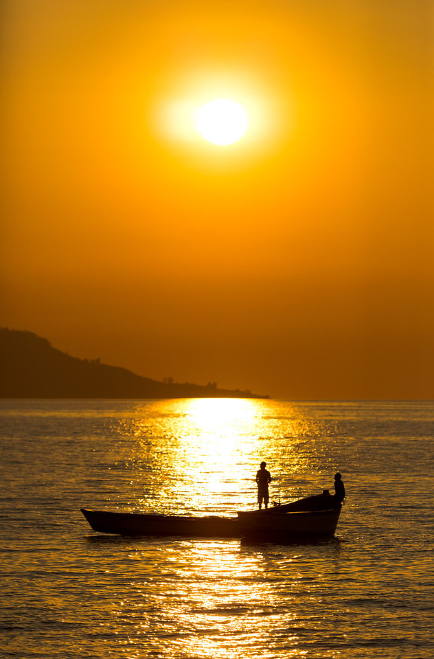 Men on fishing boats with a waning sun behind.<br /> <br /> Location: Likoma Island, Malawi<br /> <br /> Lens used: Canon 24-105mm f4.0 IS