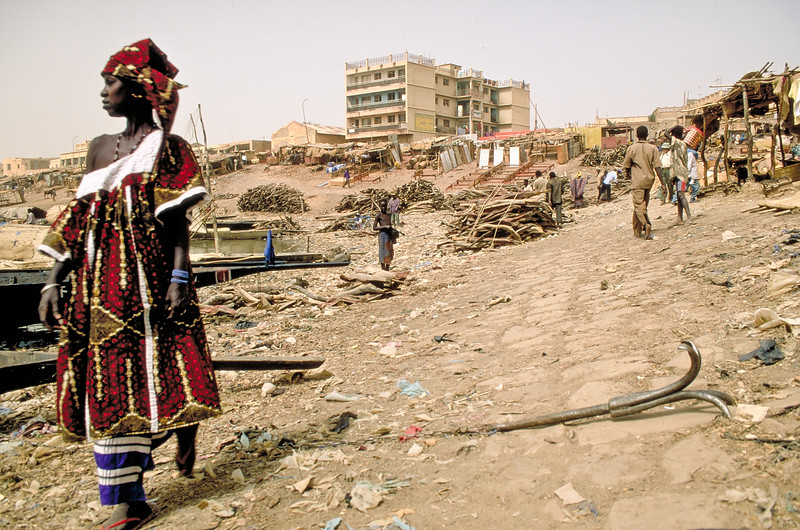 Harbour scene. Woman in front of piroges taht bring firing wood. Concrete buildings start to dominate.