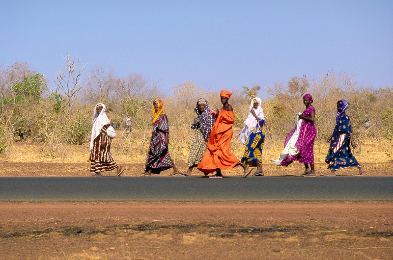 As we pause all of a sudden the sandy colours are confronted with vivid womens' dresses.