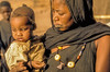Fulbe women carry their most precious treasures with them: Their children and their headdress.