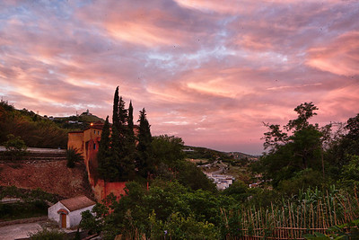 Sunrise with pink clouds on the hillside.
