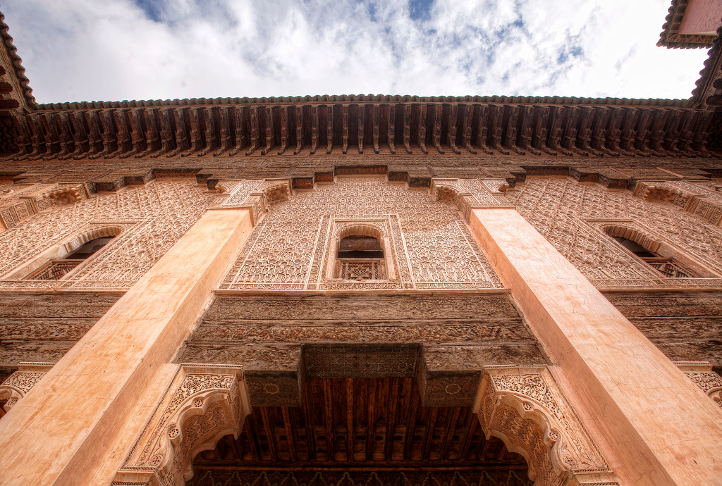 carved facade in the central courtyard of the ben youseff madrasa with blue partly cloudy sky