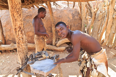Damara man making tools in blacksmith shop