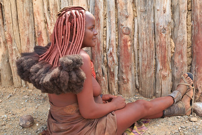 The elaborate hair style is created using a mixture of ground ochre, butter, and either goat hair or Indian hair