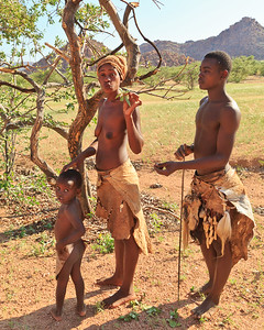 Damara man, woman, and baby   She is explaining the uses of certain plants used for everyday living and cooking