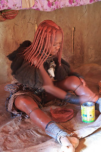Himba woman applying ochre to her body