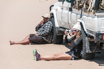 Woman taking a photo at the sand dunes of Namib Desert