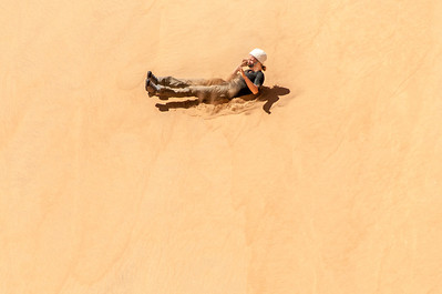 Sand boarding at the dunes of Namib Desert