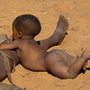 A Saan (Bushmen) Child enjoys the warm sun on his backside.