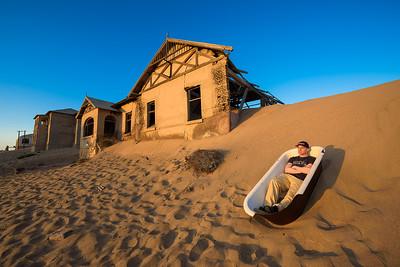 Tourist sits in a bathtub in Kolmanskop ghost town, Namibia