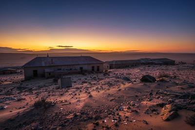 Sunrise above the abandoned houses of Kolmanskop ghost town, Namibia.