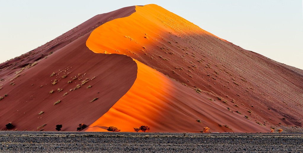the orange light of sunset as the shadows creep up the dune