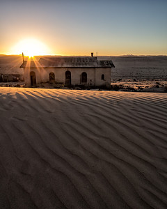 sun rise over the deserted buildings and dunes at Koolmanskuppe