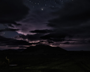 A dark mountain backlit by lightning strikes during the night