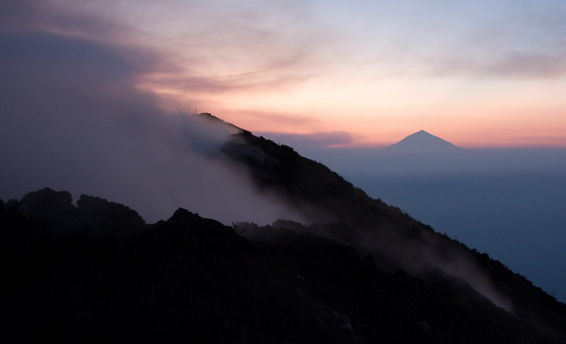 Steam and vapors escape from within the volcano crater as Rwanda's Mt. Karisimbi silhouettes as the rising sun lightens the eastern sky.<br /> <br /> Location: Nyiragongo volcano, Goma, Democratic Republic of Congo (DRC)<br /> <br /> Lens used: 24-105mm f4.0 IS