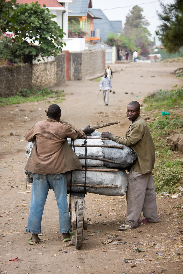 Two men load large bags of charcoal onto a chukudu, the local heavy transport.<br /> <br /> Location: Goma, Democratic Republic of Congo (DRC)<br /> <br /> Lens used: 24-105mm f4.0 IS