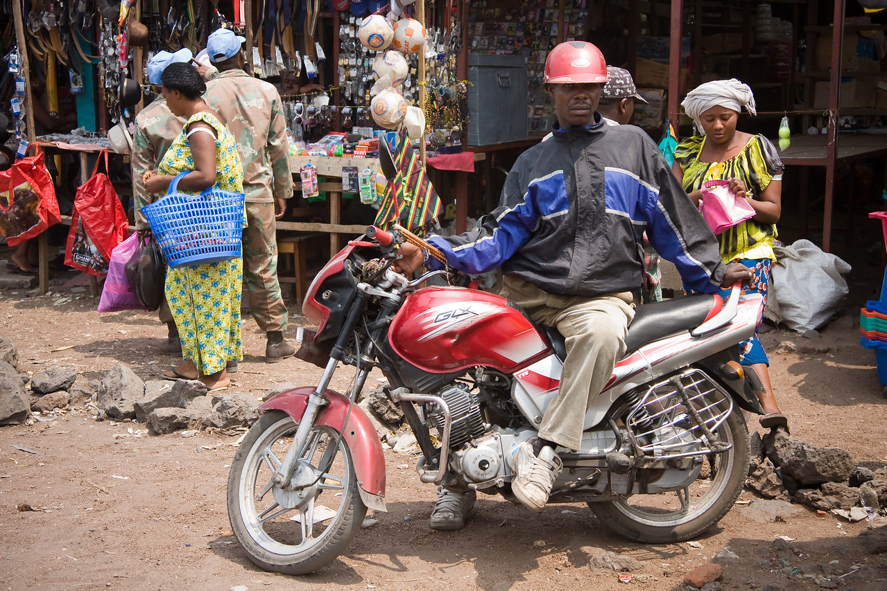 A boda-boda (motorcycle taxi) driver eyes me as a potential fare at the town market.<br /> <br /> Location: Goma, Democratic Republic of Congo (DRC)<br /> <br /> Lens used: 24-105mm f4.0 IS