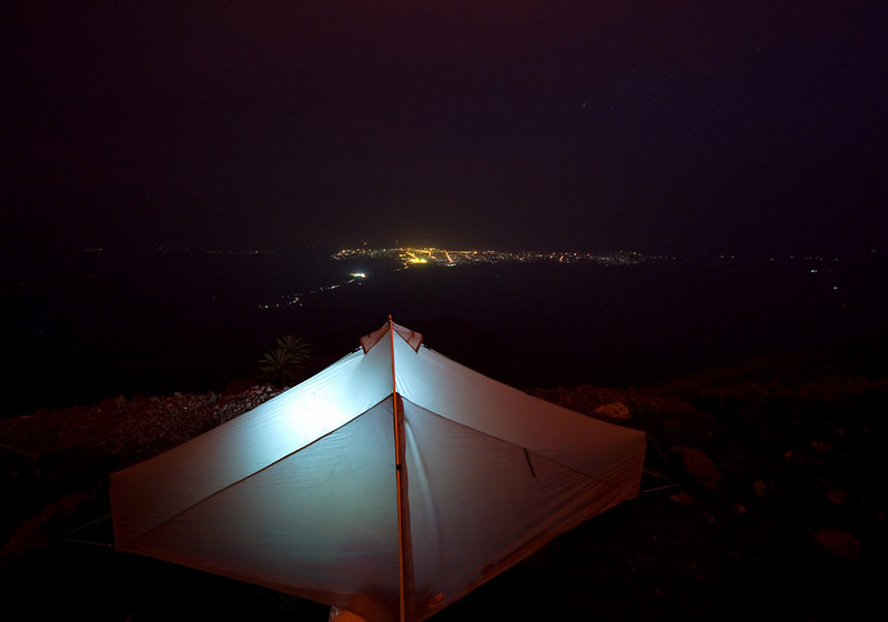 My tent, illuminated from within set up on the summit of the volcano with the glowing lights of the city of Goma behind.<br /> <br /> Location: Nyiragongo volcano, Goma, Democratic Republic of Congo (DRC)<br /> <br /> Lens used: 10-22mm f3.5-4.5