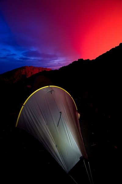My tent, illuminated from within set up at the summit of the volcano. The red glow behind is from the lava lake inside the crater and the blue is the darkening evening sky.<br /> <br /> Location: Nyiragongo volcano, Goma, Democratic Republic of Congo (DRC)<br /> <br /> Lens used: 10-22mm f3.5-4.5