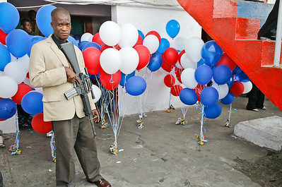 MONROVIA - LIBERIA , MARCH 2 2007 : SSS officer - Secret Service officer with machine gun standing in front of some ballons.    (Photos by : Christopher Herwig )
