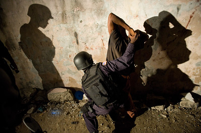 UNMIL Photo/Christopher Herwig, November 9 2008, Monrovia, Liberia - ERU Officer secures a drug suspect against wall.  The suspects are taken by surprise and some resist. The UNPOL advisors remind them to be clear in their demands and not to use unnecessary force.