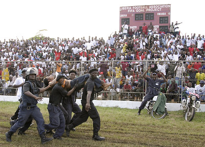 MONROVIA, LIBERIA - OCTOBER, 2006:  Fans and police celebrate a goal by Liberia against Rwanda as riot police carry off an injured female spectator.  (Photo by: Christopher Herwig)