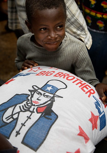 FREETOWN, SIERRA LEONE - AUGUST,2006: Young boy beside a big bag of Big Brother Rice. The underdeveloped district of Kroo Town. (Photo by: Christopher Herwig)