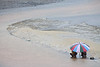 FREETOWN PENINSULA, SIERRA LEONE - AUGUST,2006: A young boy and girl with umbrella on the rainy beach. Beaches around the village of Sussex on the Freetown Peninsula. (Photo by: Christopher Herwig)